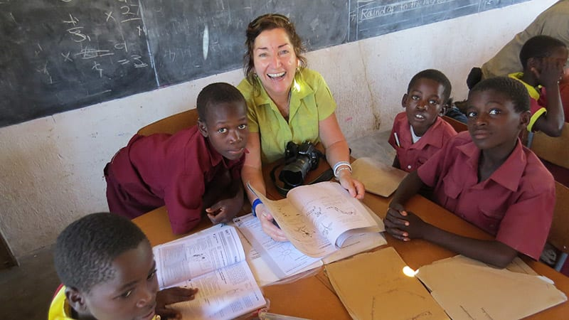 Traveler reading with students in Zimbabwe classroom