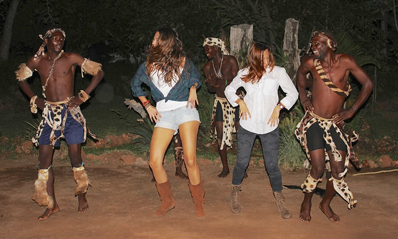 Travelers dancing with men doing traditional dance in Zimbabwe