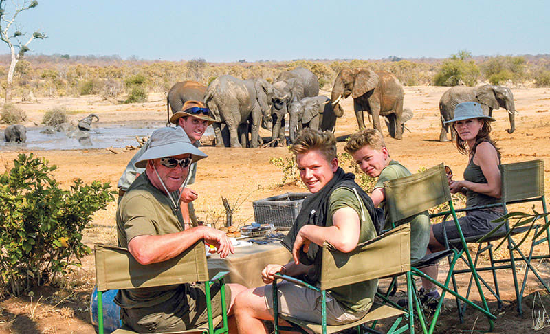 Group of travelers on safari in Zimbabwe having snacks near herd of elephants