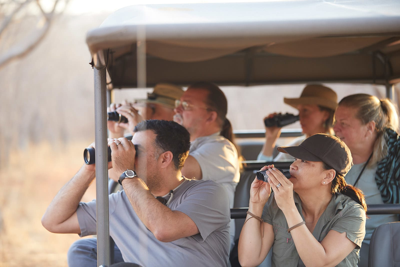 Group of travelers using binoculars from open-air jeep on safari in Zimbabwe