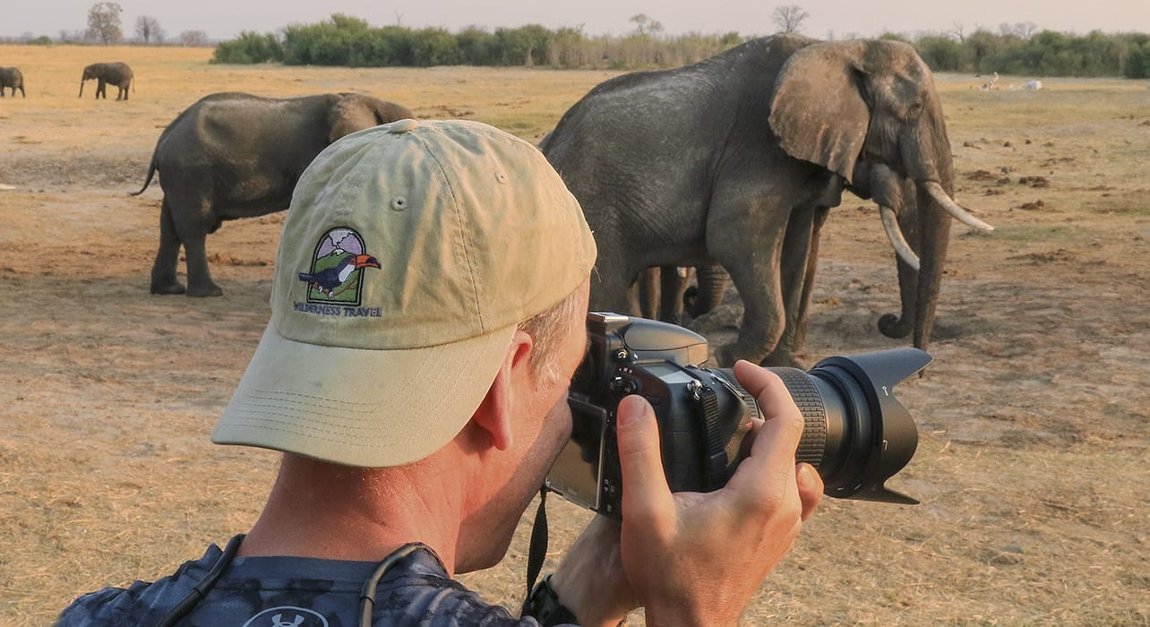 Traveler wearing Wilderness Travel hat taking photo of elephants in Zimbabwe