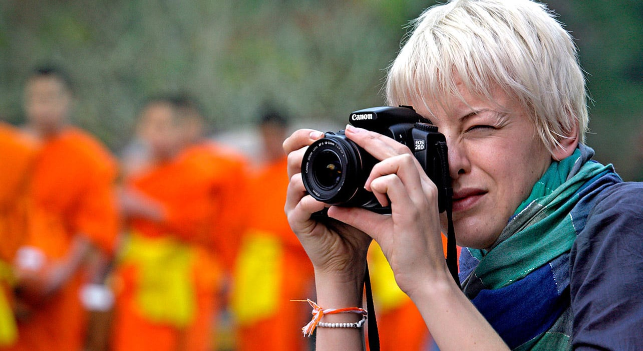 woman photographing monks