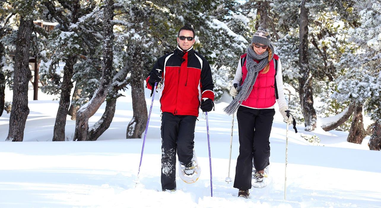 6 slide happy couple snowshoeing lapland finland pano