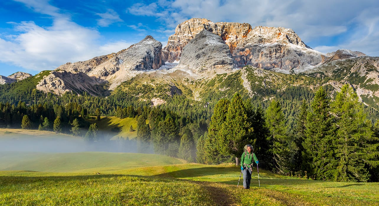 hiker italy dolomites pasture