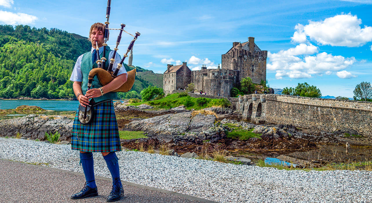 eilean donan castle scotland bagpiper kilt