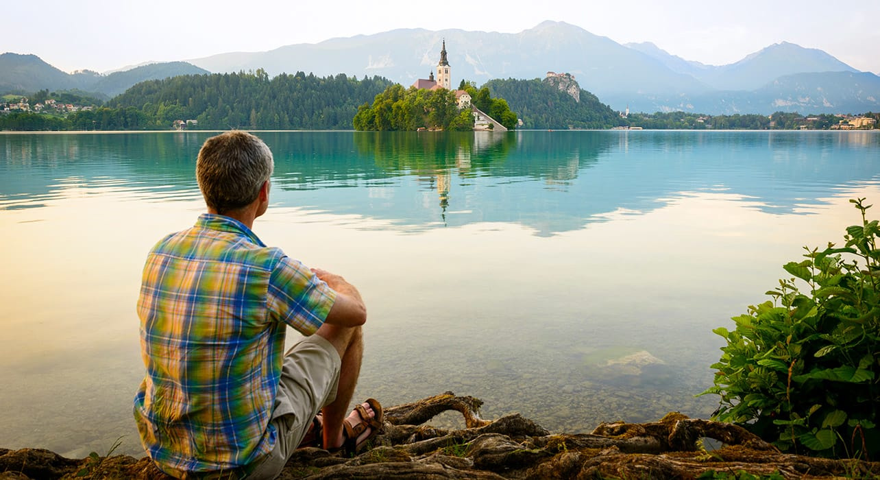 slovenia man sitting on the bank of lake bled cradj