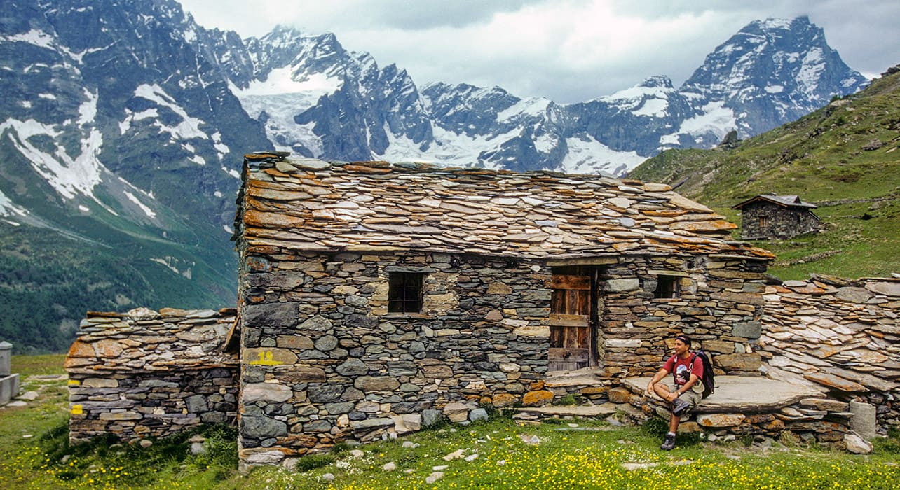 hiker resting at stone hut