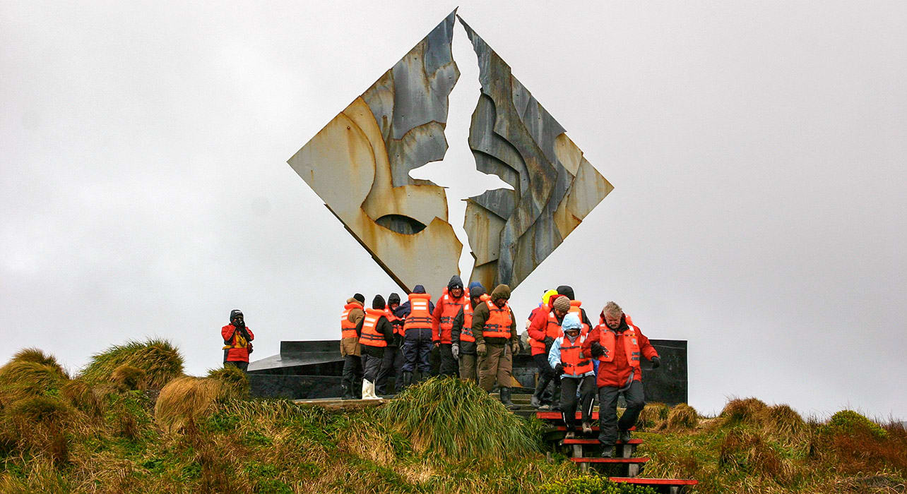 tourists at cape horn monument cold