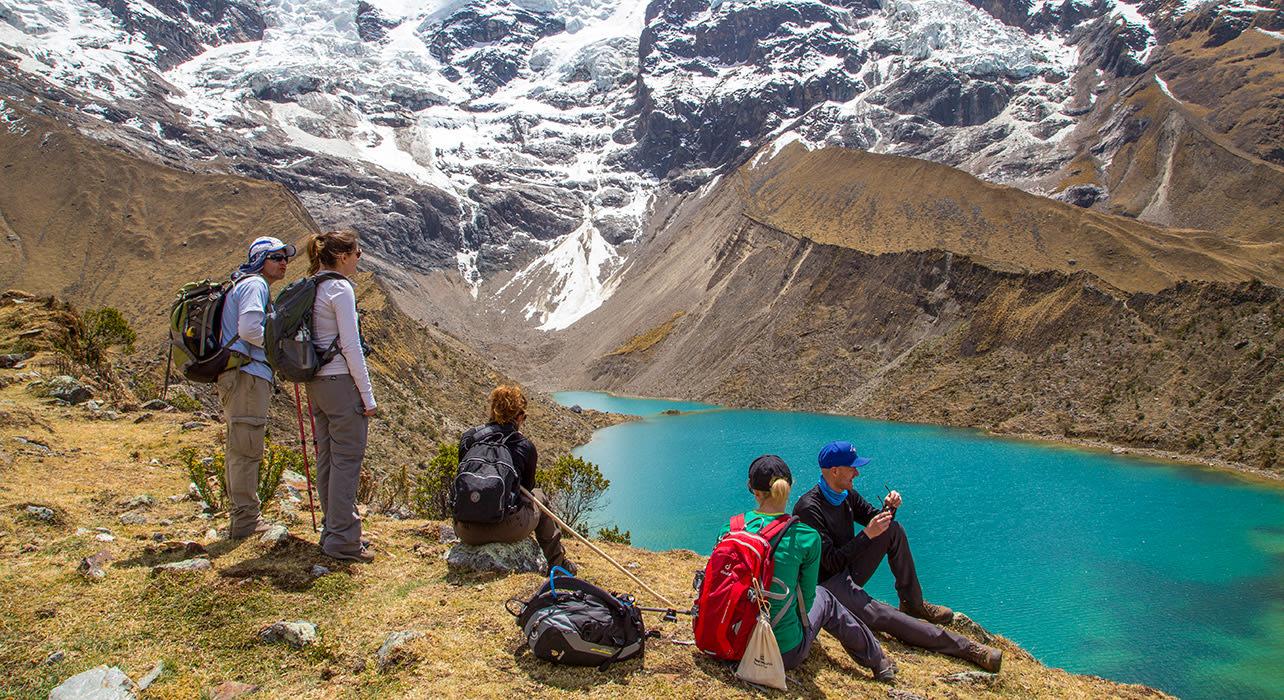 2 slide salkantay trek hikers above glacial lake pano