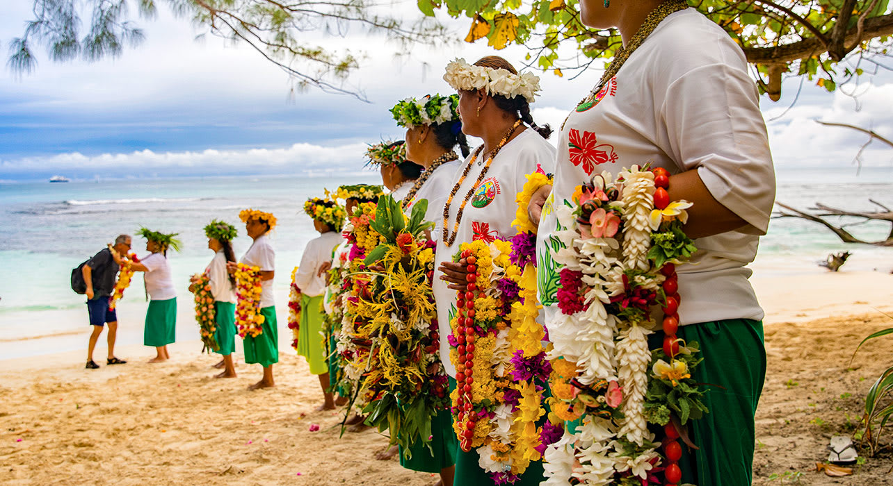 greeting guests on beach with flower leis