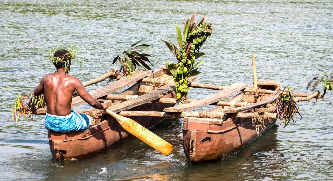 vanuatu man paddling traditional boat