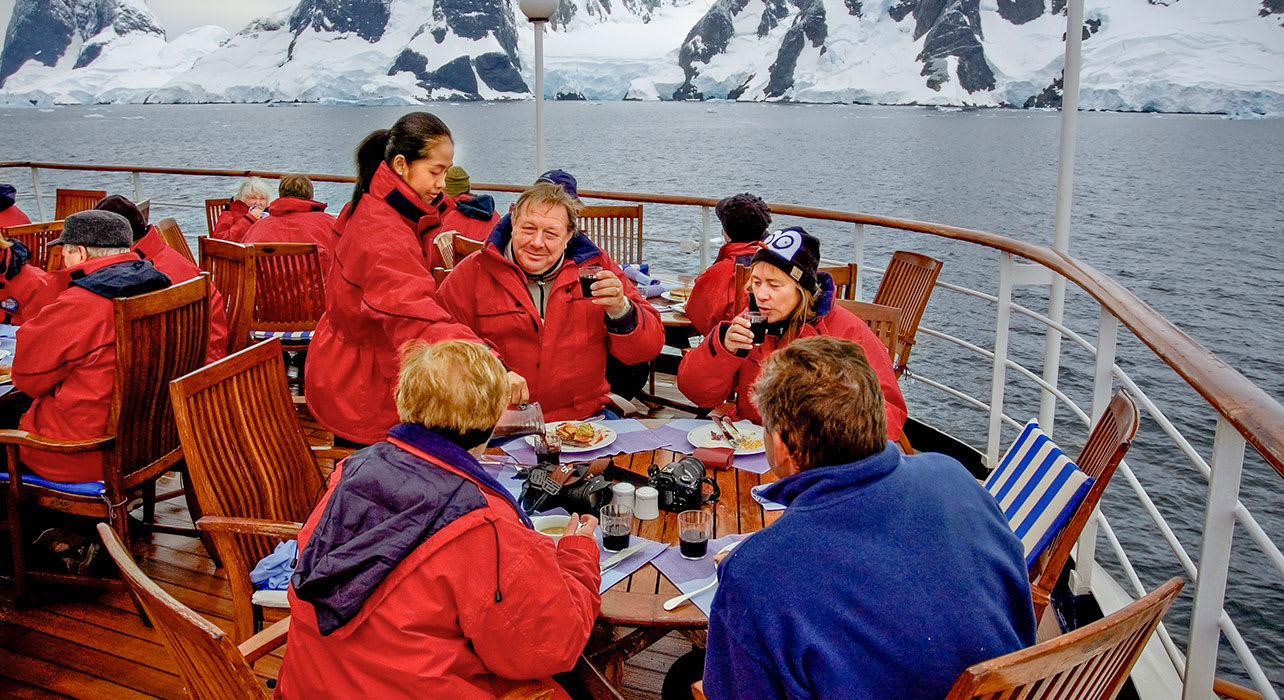 clients enjoying a meal on deck of ship