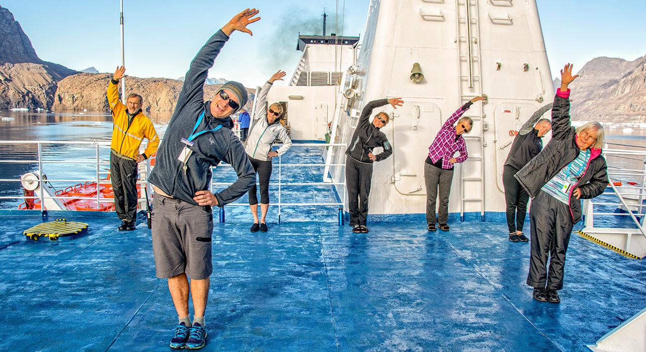 canada greenland karrat fjord passengers stretching yoga on boat