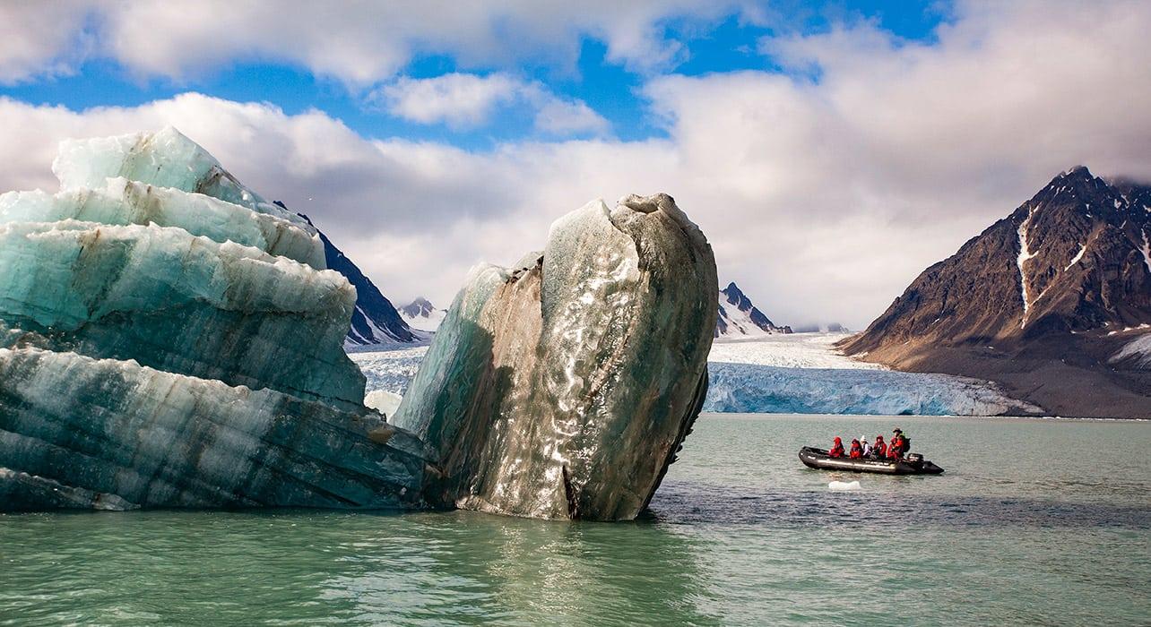 norway svalbard greenland zodiac rounding iceberg