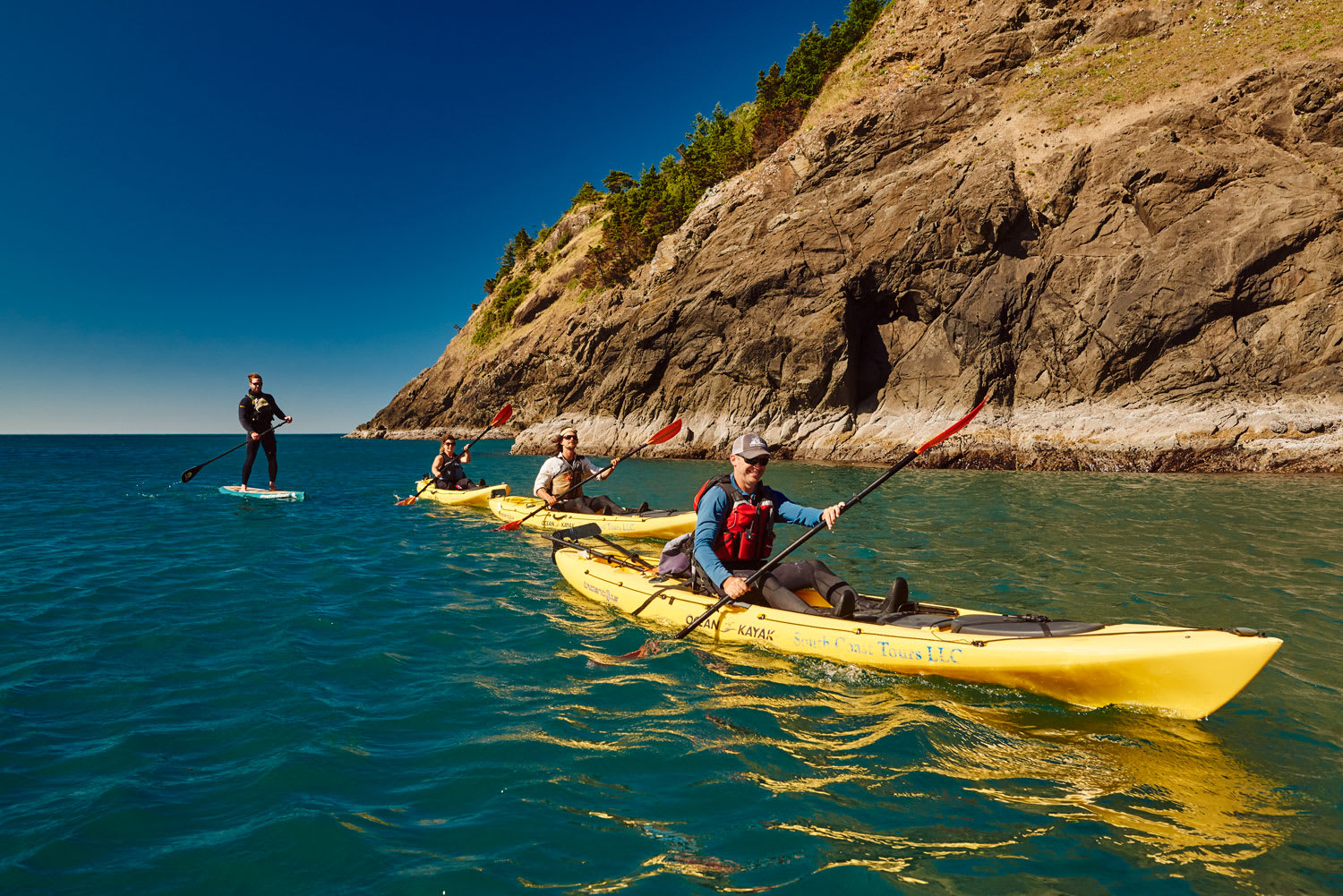 kayakers and a paddle boarder paddling along rocks near Port Orford, Oregon
