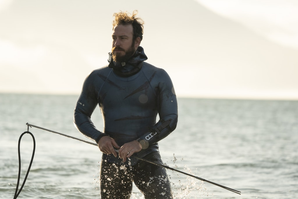 Freediver Grant Hogan walking out of the Pacific ocean at sunrise in a wetsuit holding a fishing spear