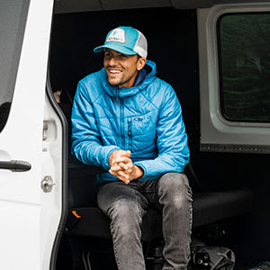 Photographer Justin Myers smiling while sitting on the step of a van