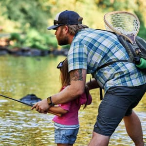 A man teaching a young girl to fly fish