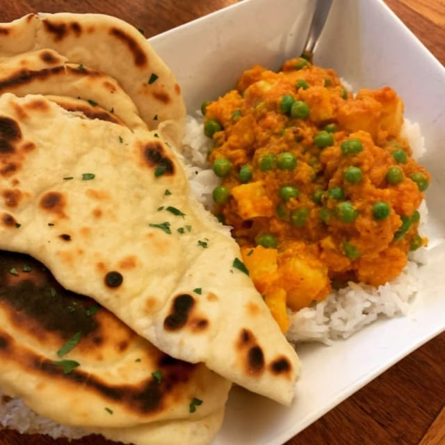Several torn-off peices of naan atop a bowl of rice and aloo paneer.
