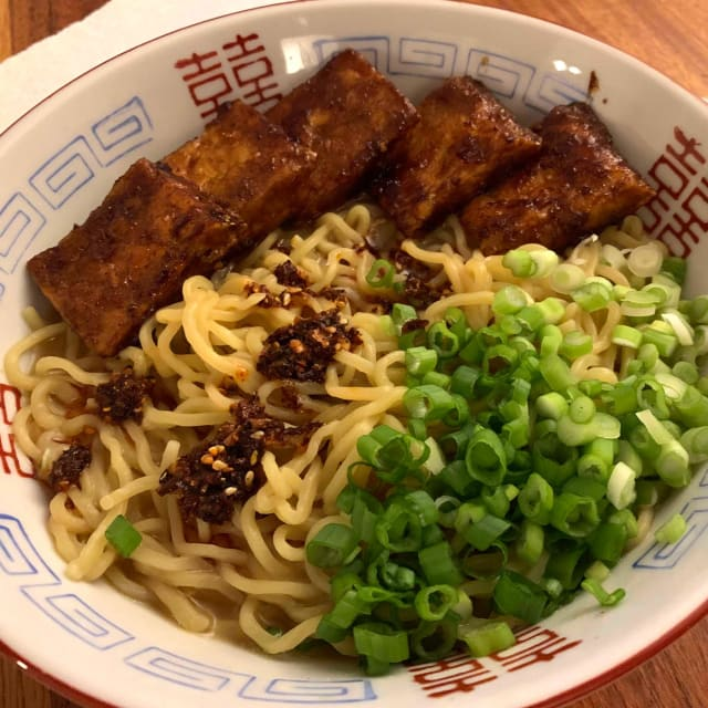 A bowl of noodles topped with a handful of green onions and strips of sticky red tofu