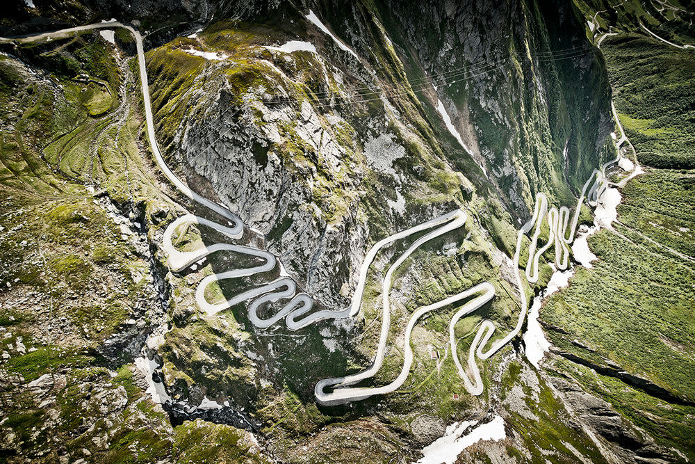 """Die alte Straße hoch zum Gotthardpass – auch bekannt als """"Via Tremola"""" oder die Straße des Zitterns – ist legendär. Autofahrer rüttelt es auf dem Kopfsteinpflaster der historischen Nord-Süd-Verbindung ordentlich durch. Die Landschaft ist rau, der Wind kräftig, eine Pause auf der Passhöhe empfiehlt sich aber nicht nur wegen des Ausblicks: Die Bratwürste vom Grill gehören zu den besten der Alpen. Höhe — 2.091 m"""