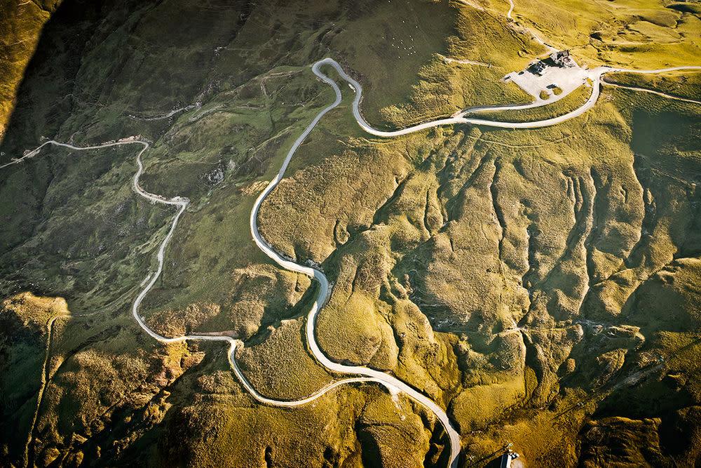 Für Fotograf Stefan Bogner ist sein Porsche 911 der perfekte Begleiter, um Straße und Natur zu erfahren. Die Anreise zum Col d'Aubisque dauert gut zwei Tage, aber das Ziel lohnt sich: Am Pass, der zur Tour-de-France-Strecke gehört, zieht sich jede Kurve ewig, Bäume gibt es kaum. Und die grüne Hochebene vermittelt einem das Gefühl, auf weichen Grasmatten unterwegs zu sein. Höhe — 1.709 m