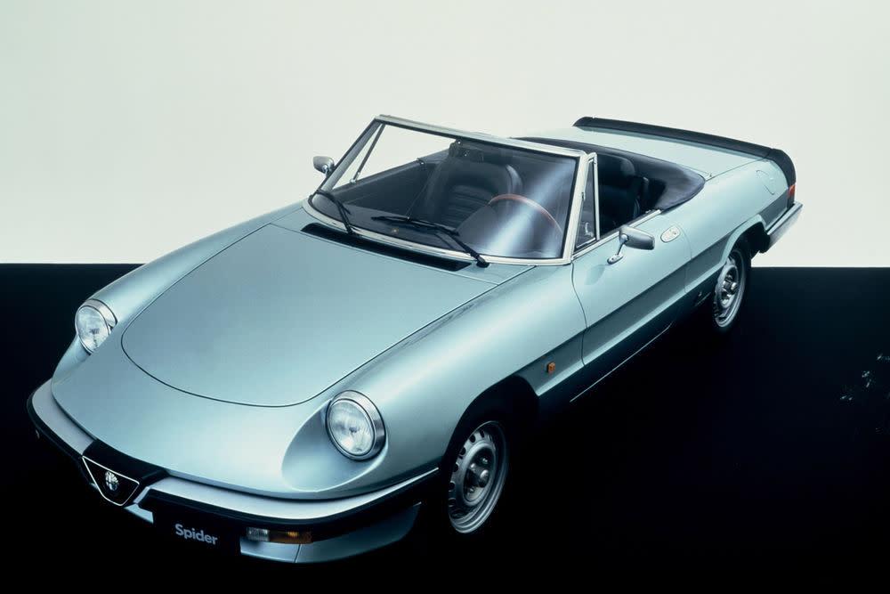 """Mit dem Käfer eroberten wir Italien von Norden aus. Der Alfa Romeo Spider war der Gegenschlag aus dem Süden. Kaum ein Auto vermittelte besser das Gefühl von Wärme und Sommerwind als der Spider. Zwischen 1966 und 1993 wurden vier Baureihen in minimaler optischer Veränderung produziert. Auftritte wie in """"Die Reifeprüfung"""" mit Dustin Hoffmann taten ein Übriges, um den Mythos des Spiders festzuschreiben - hier in der Aerodynamika-Version, die zwischen 1983 und 1989 hergestellt wurde."""