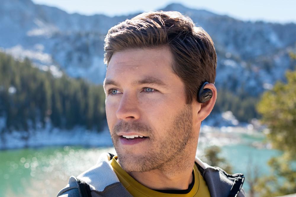 Die Bose Sport Open Earbuds werden über dem Gehörgang an die Ohrmuschel gehängt.