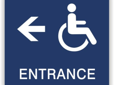 Disabled entrance directional sign with tactile and braille lettering.