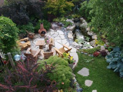 Flagstone patio, muskoka chairs and chiminea by a pond.
