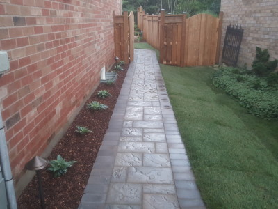 Techo Bloc blue pathway leads into a beautiful backyard