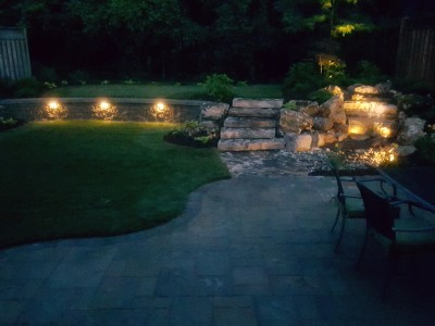 Backyard with a pondless waterfall lighting, and under cap wall lights
