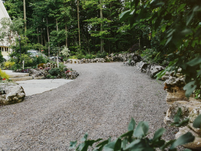 farmhouse gravel driveway with boulders retaining