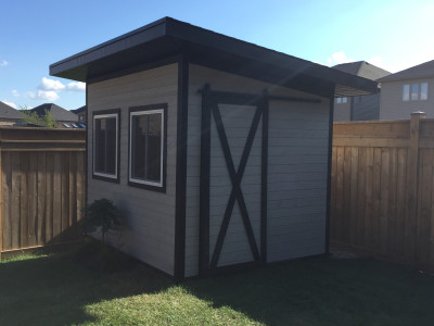 Backyard shed with barn style door. Maibec Siding - ocean grey