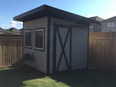 Backyard shed with barn style door. Maibec Siding - ocean grey