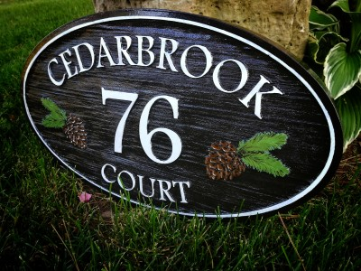 Engraved cedar house sign with painted details.