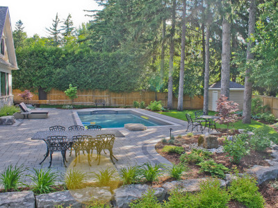 Tasteful garden beds compliment this expansive backyard pool deck.