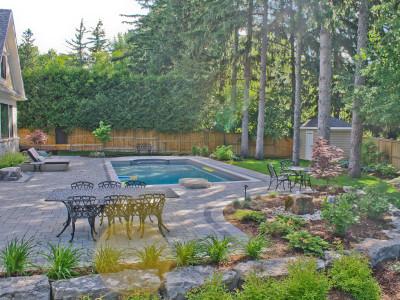 Tasteful garden beds compliment this expansive backyard pool deck.
