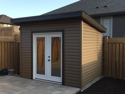 A cute backyard shed with garden doors.