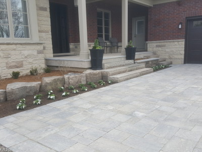 Beautiful paver driveway, natural stone steps, and flagstone porch