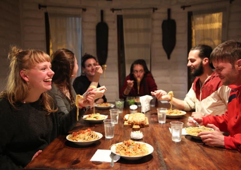 grupo de viajantes de diferentes parte do mundo jantando em hostel
