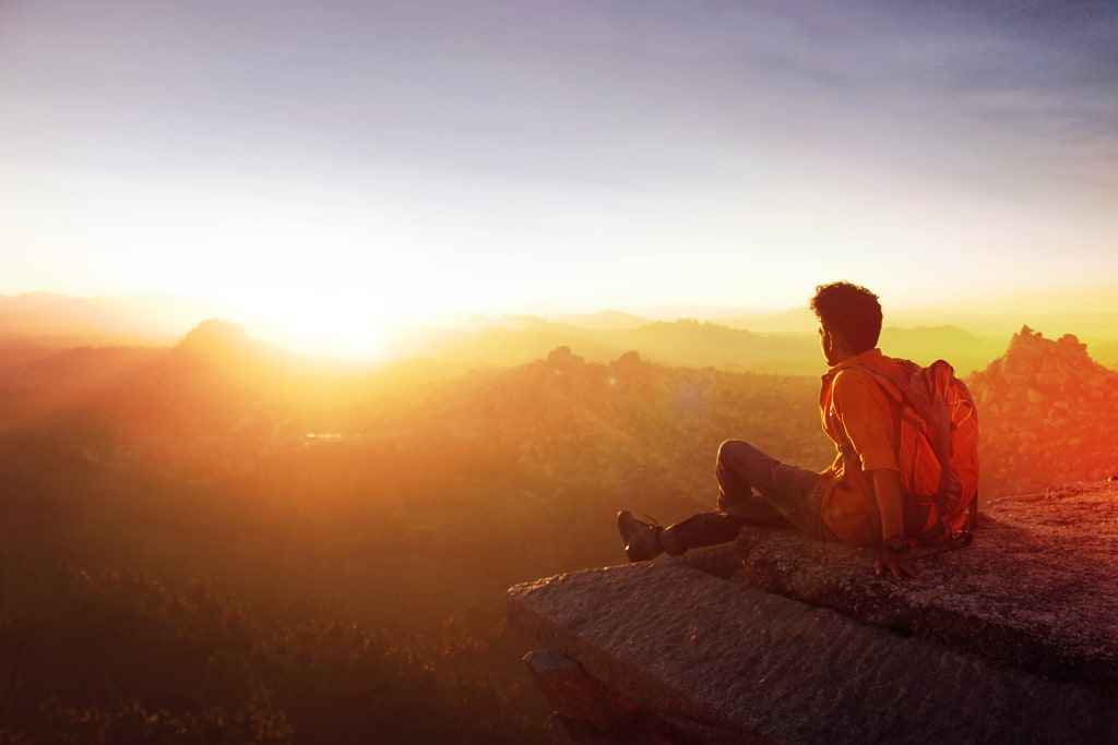 Homem viajando sozinho no alto de uma montanha