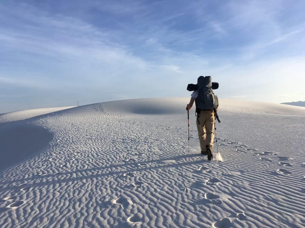 Homem escalando montanha nevada