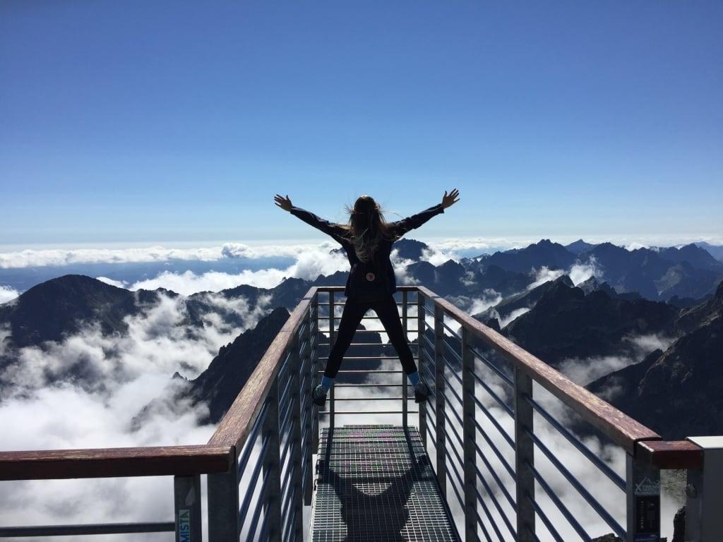 mulher em mirante no pico de uma montanha