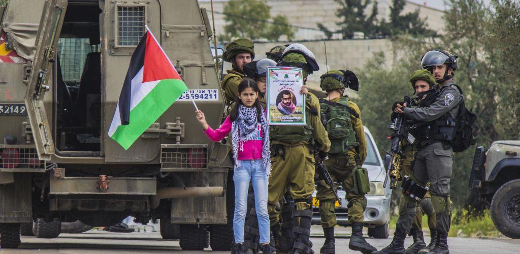 Garota palestina protesta em frente a soldados israelenses que bloqueiam as vias de seu vilarejo