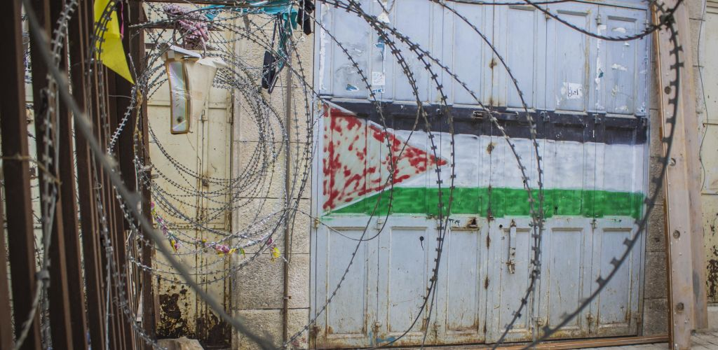 bandeira da Palestina pintada em muro e alguns arames farpados perto