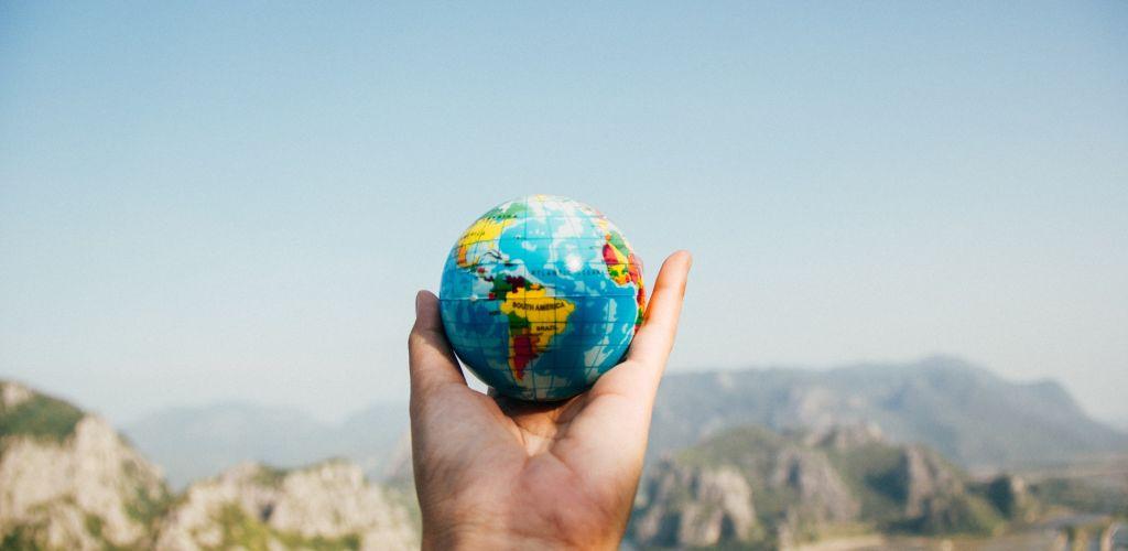Uma mão segurando um globo terrestre e ao fundo paisagem de montanhas