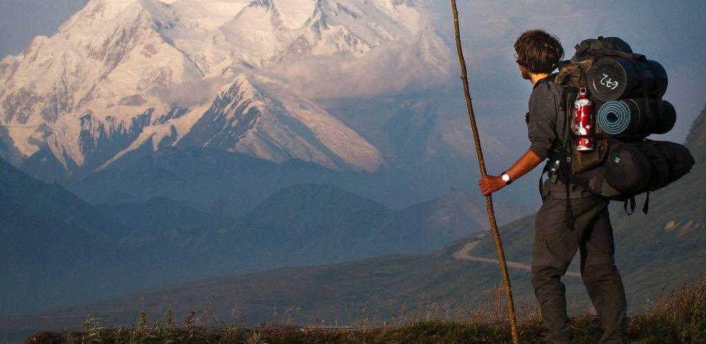 Homem caminhando por montanhas do Alasca