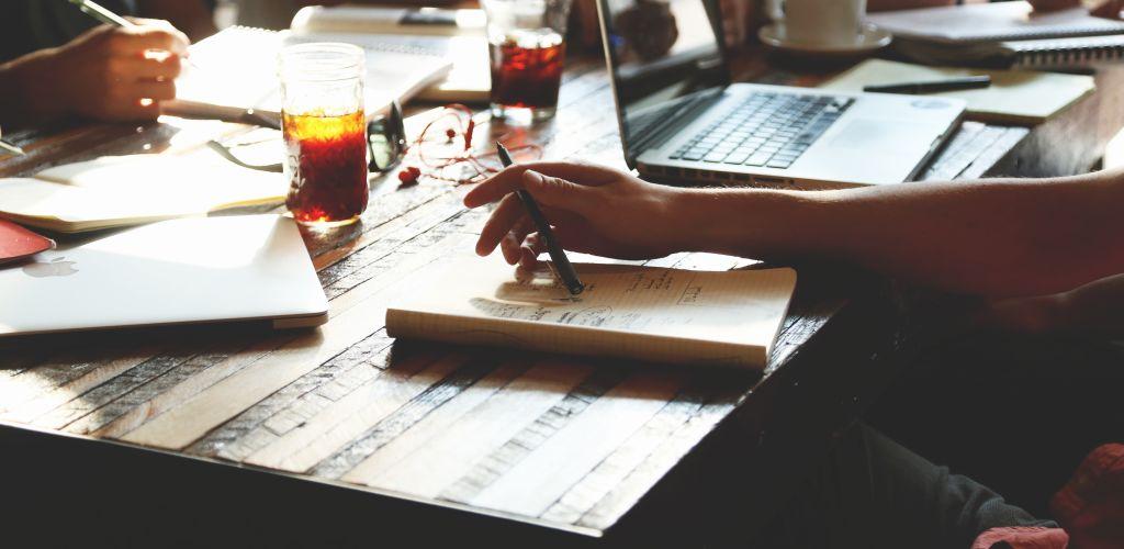 maos escrevendo em cadernos em  uma reunião