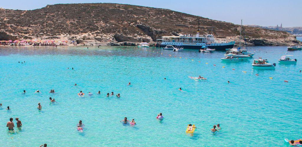 mar azul em Malta com muitos turistas